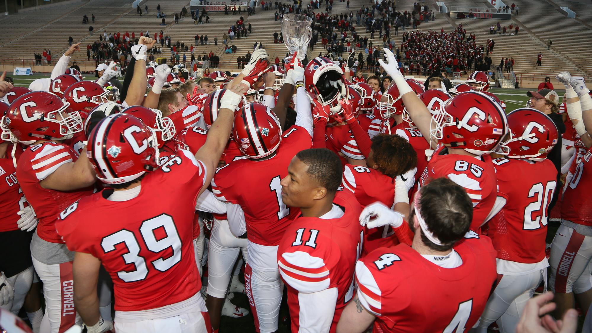 The Cornell football team celebrates with the Empire State Bowl after a 35-9 win over Columbia on Saturday, Nov. 23, 2019 at Schoellkopf Field in Ithaca, N.Y.